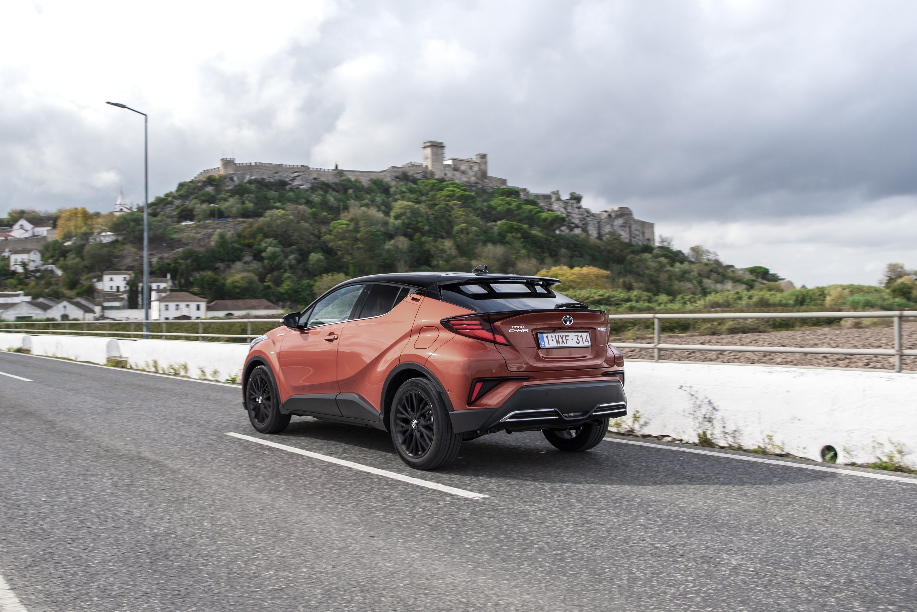 Rear view of a Toyota C-HR driving on a road