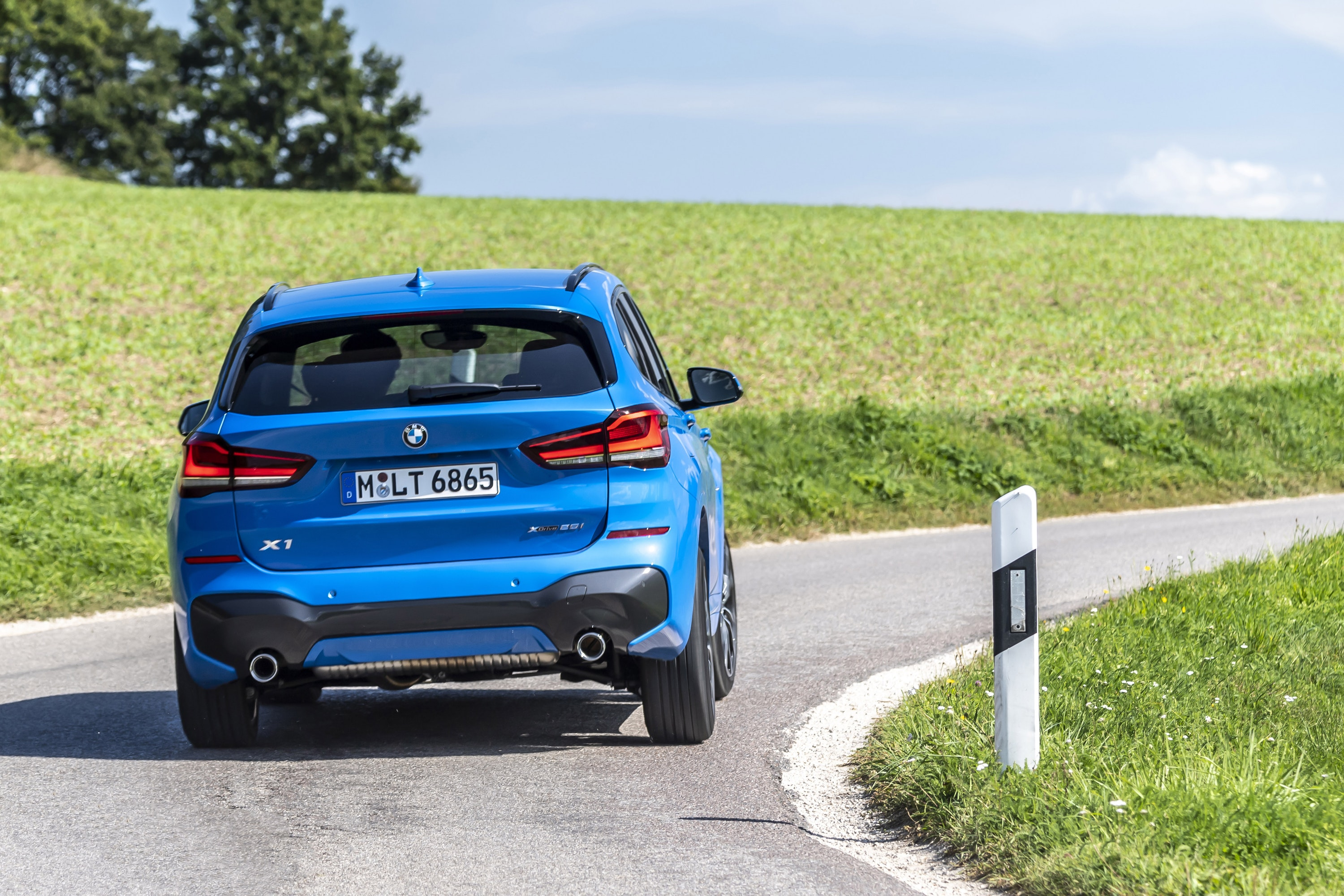 Rear view of a BMW X1 driving around a corner