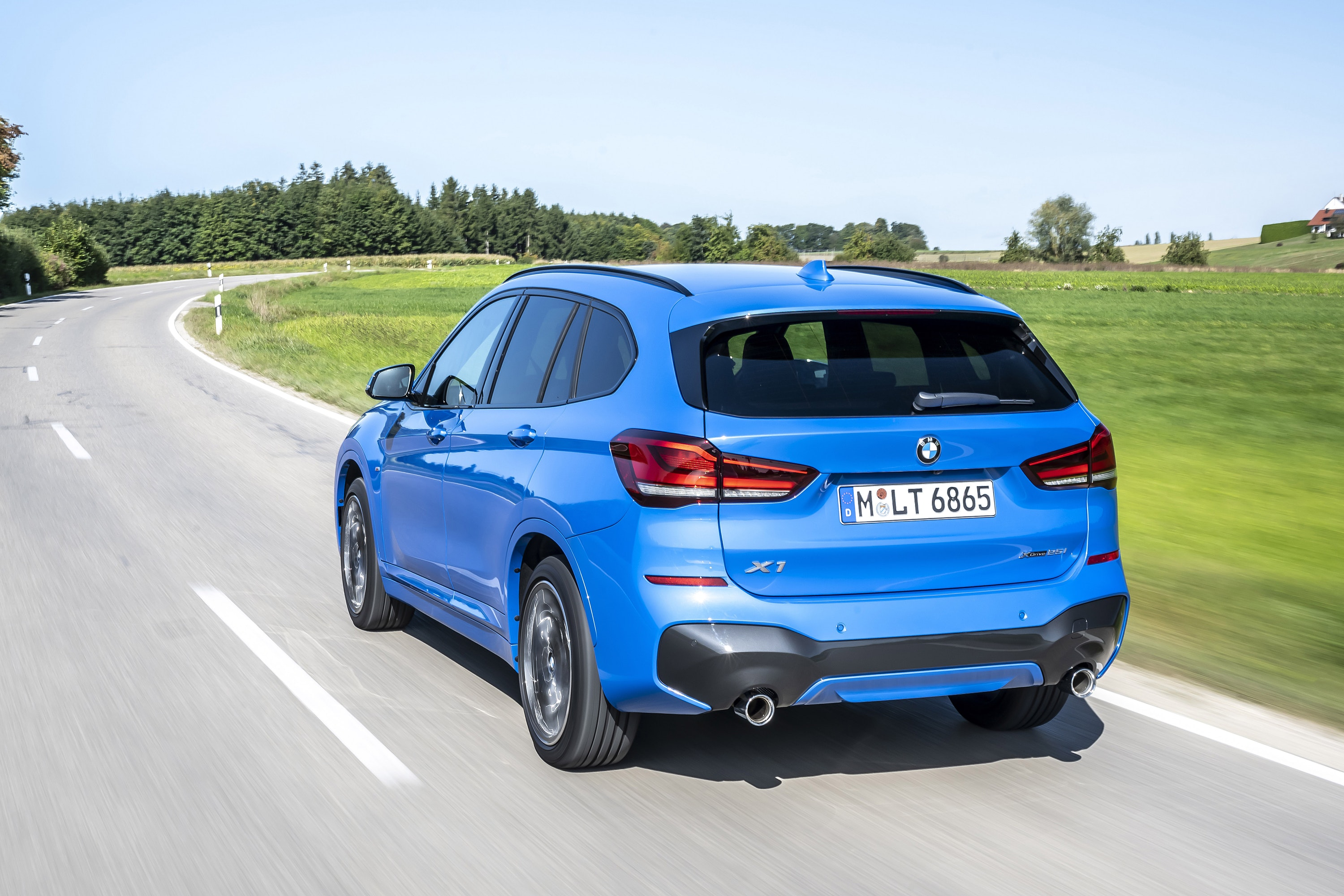 Rear view of a BMW X1 driving on a road
