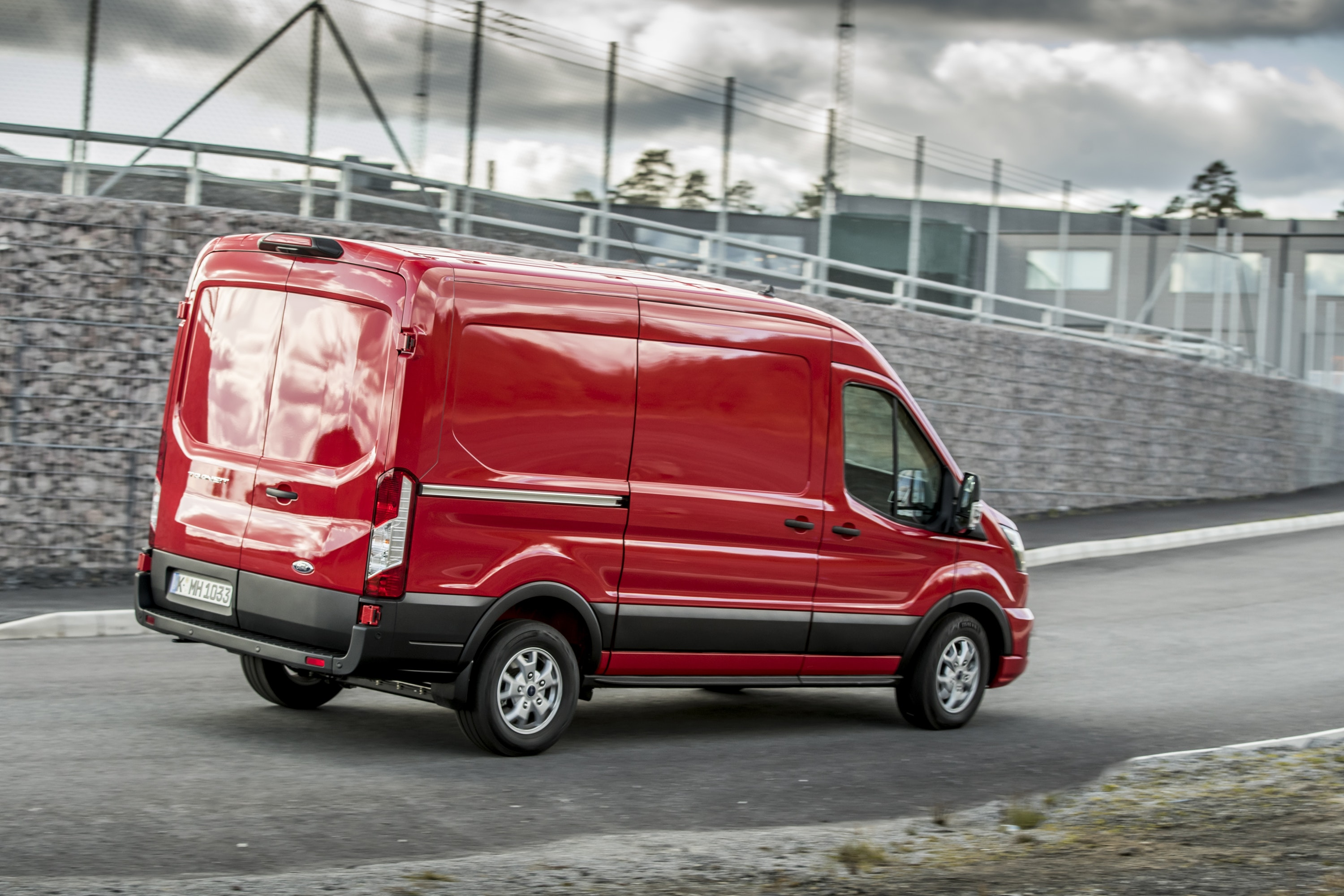 Side view of a Red Ford Transit