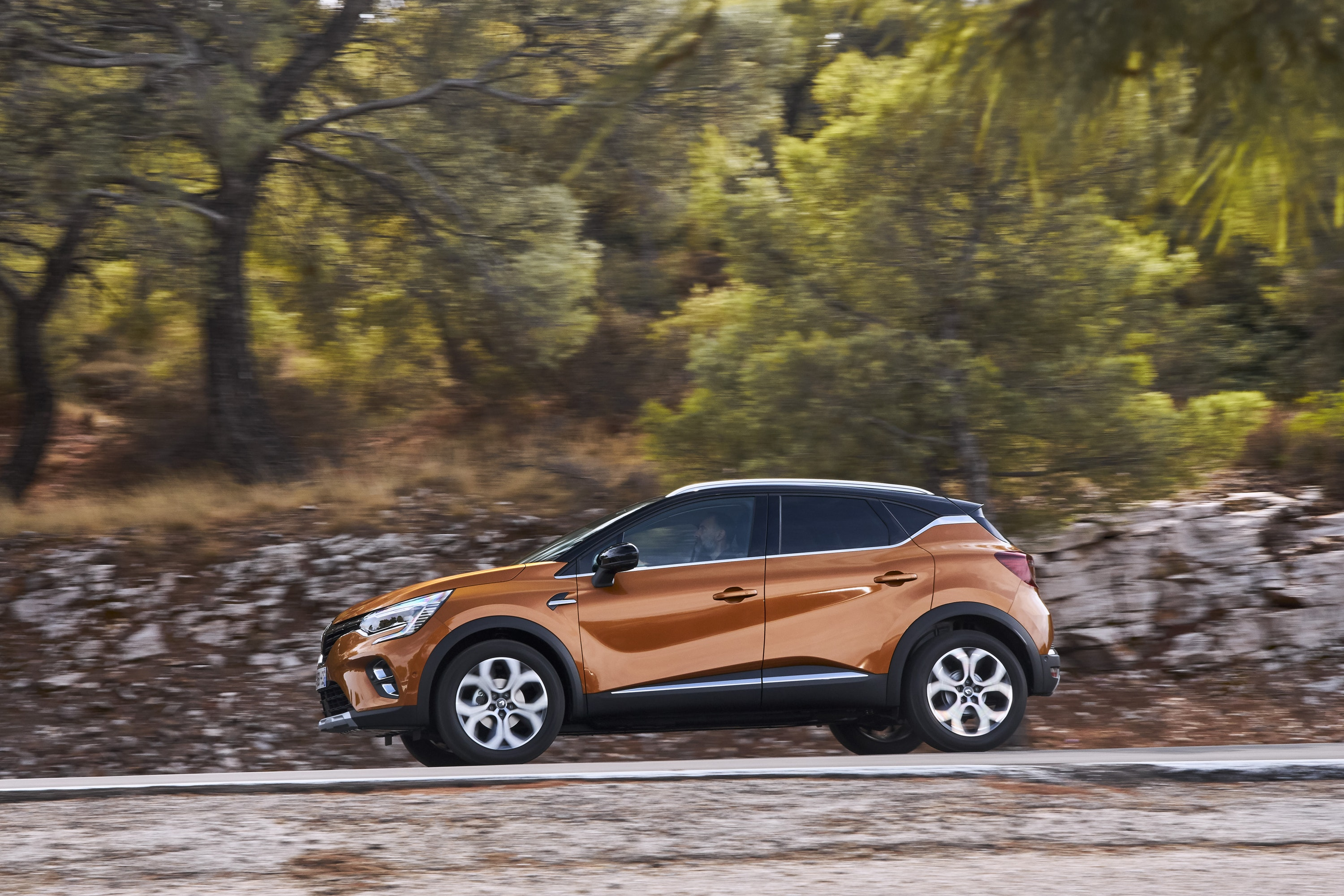 side view of Renault Captur driving on a road