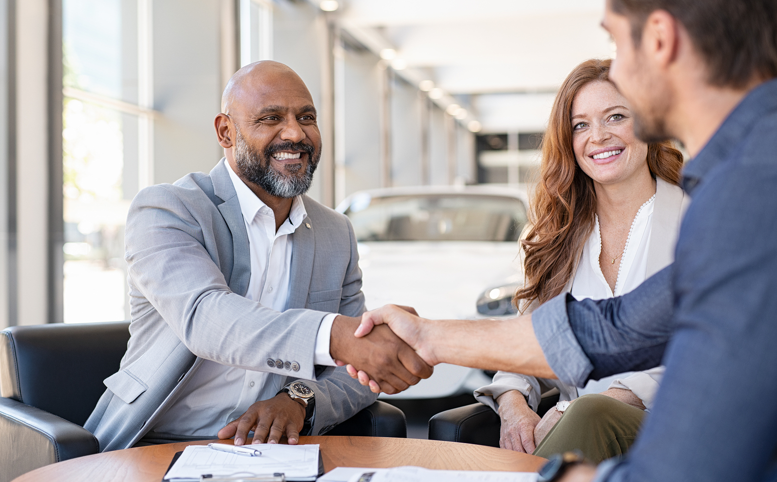 Happy sales advisor shaking hands with man after signing contract