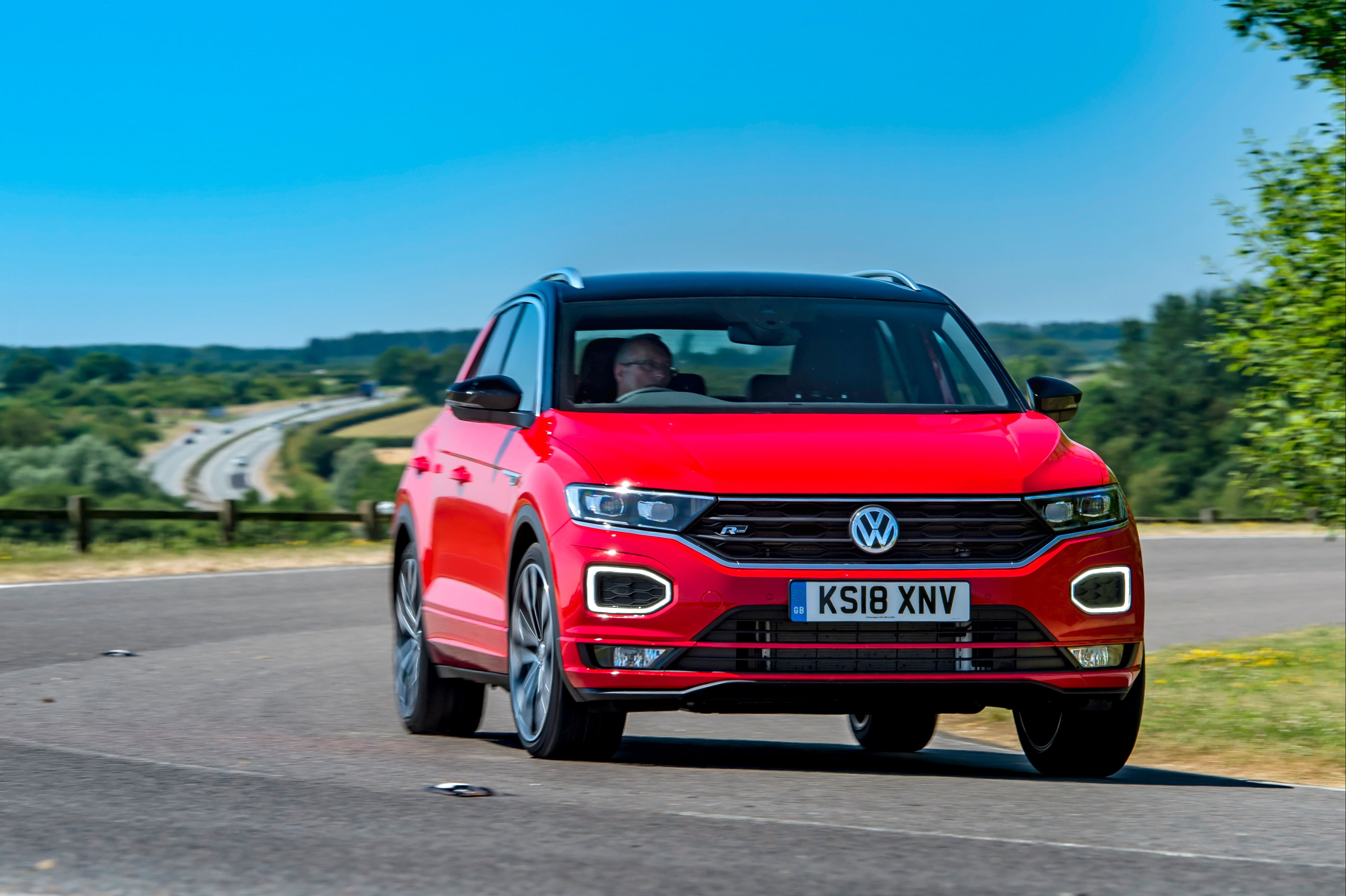 Bright red Volkswagen T-Roc driving towards you with a very blue sky