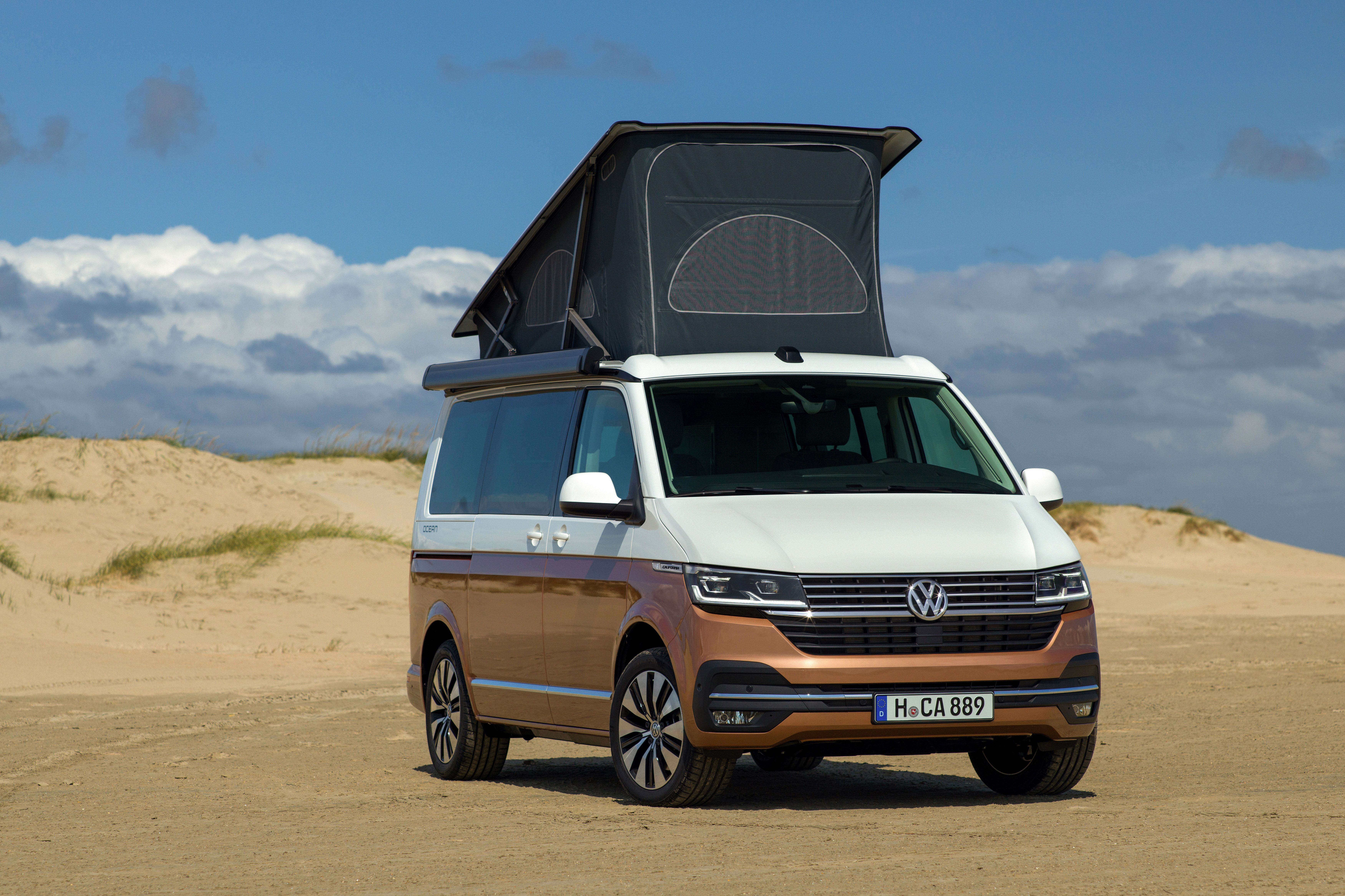 Two tone VW California on the beach with the roof up