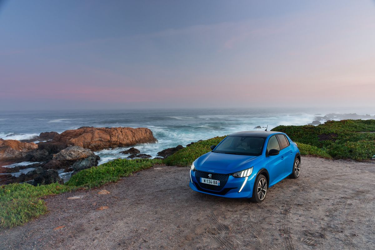 peugeot e 208 parked in front of the beach
