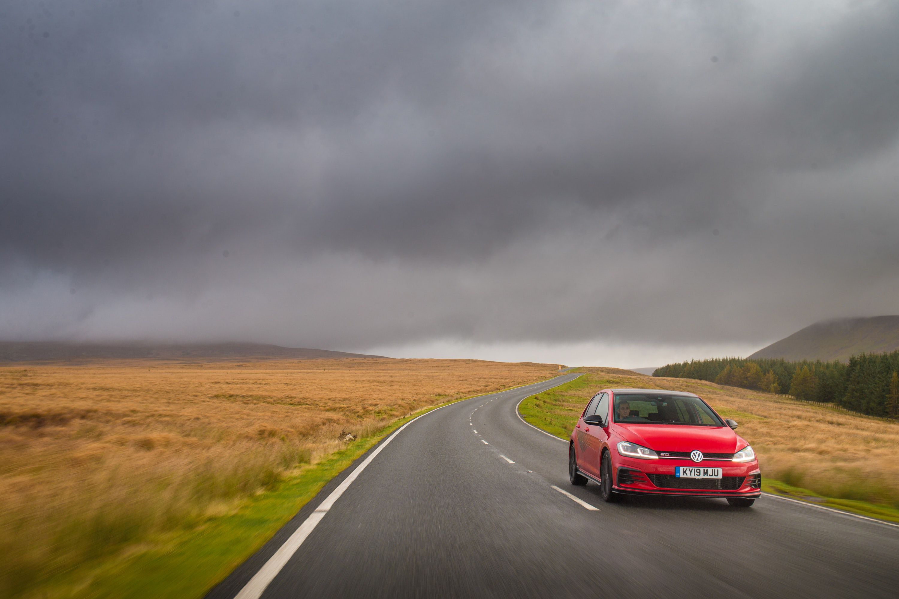 Red golf driving on dry roads