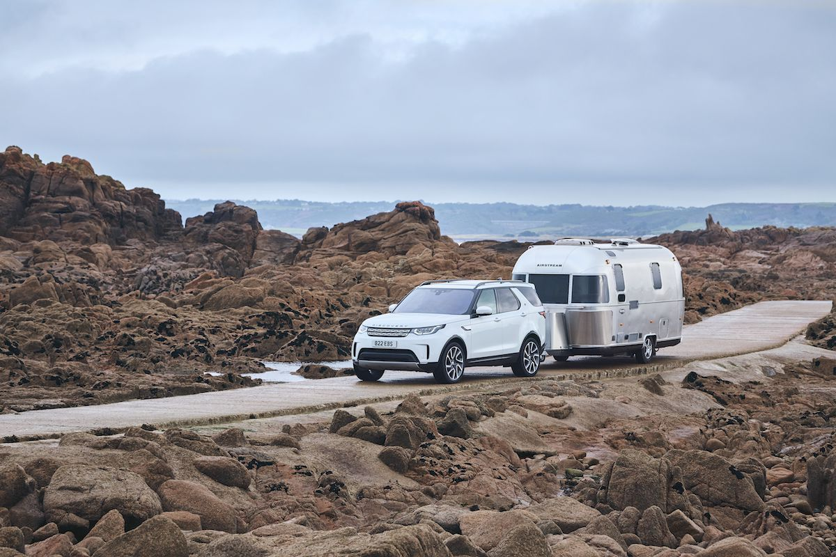 Land Rover discovery towing a caravan down a dirt road