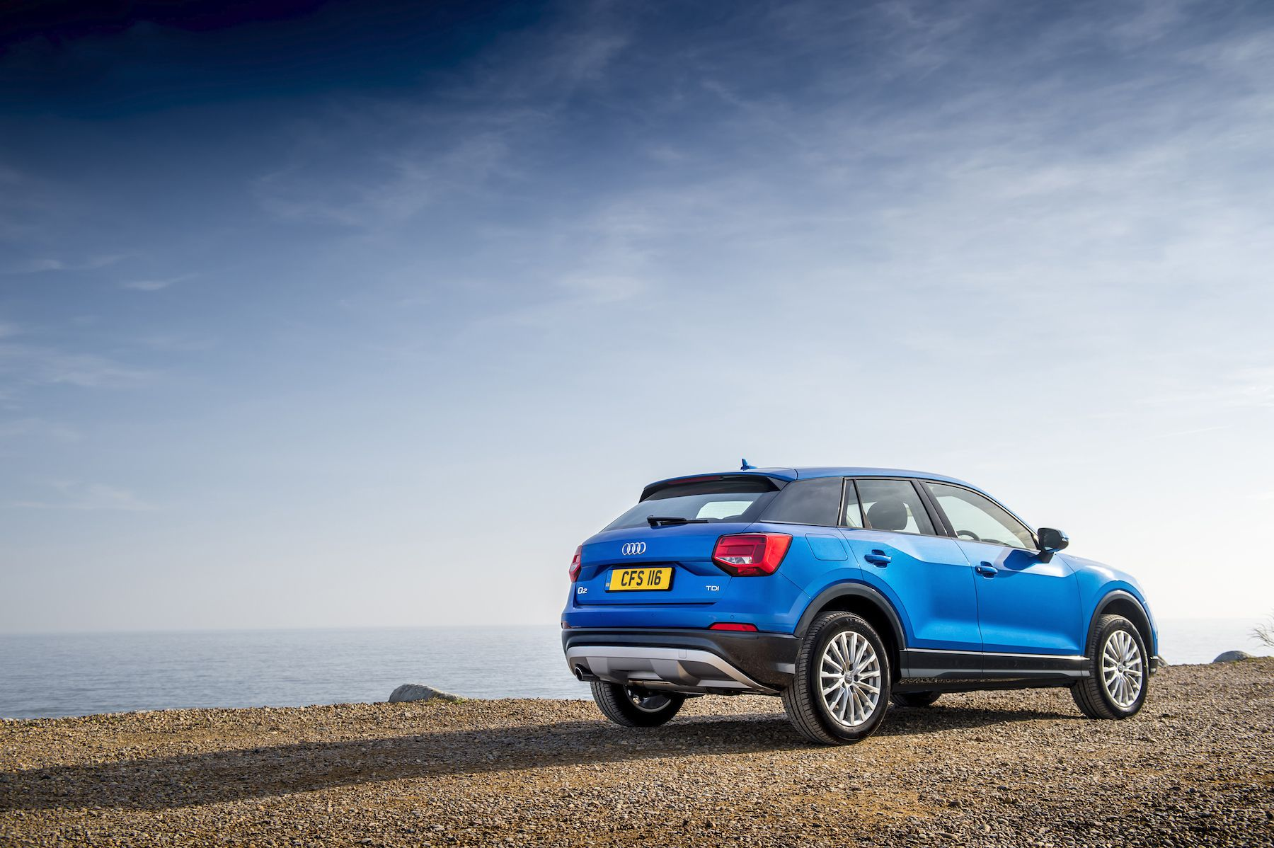 Blue Audi Q2 SUV by beach from rear