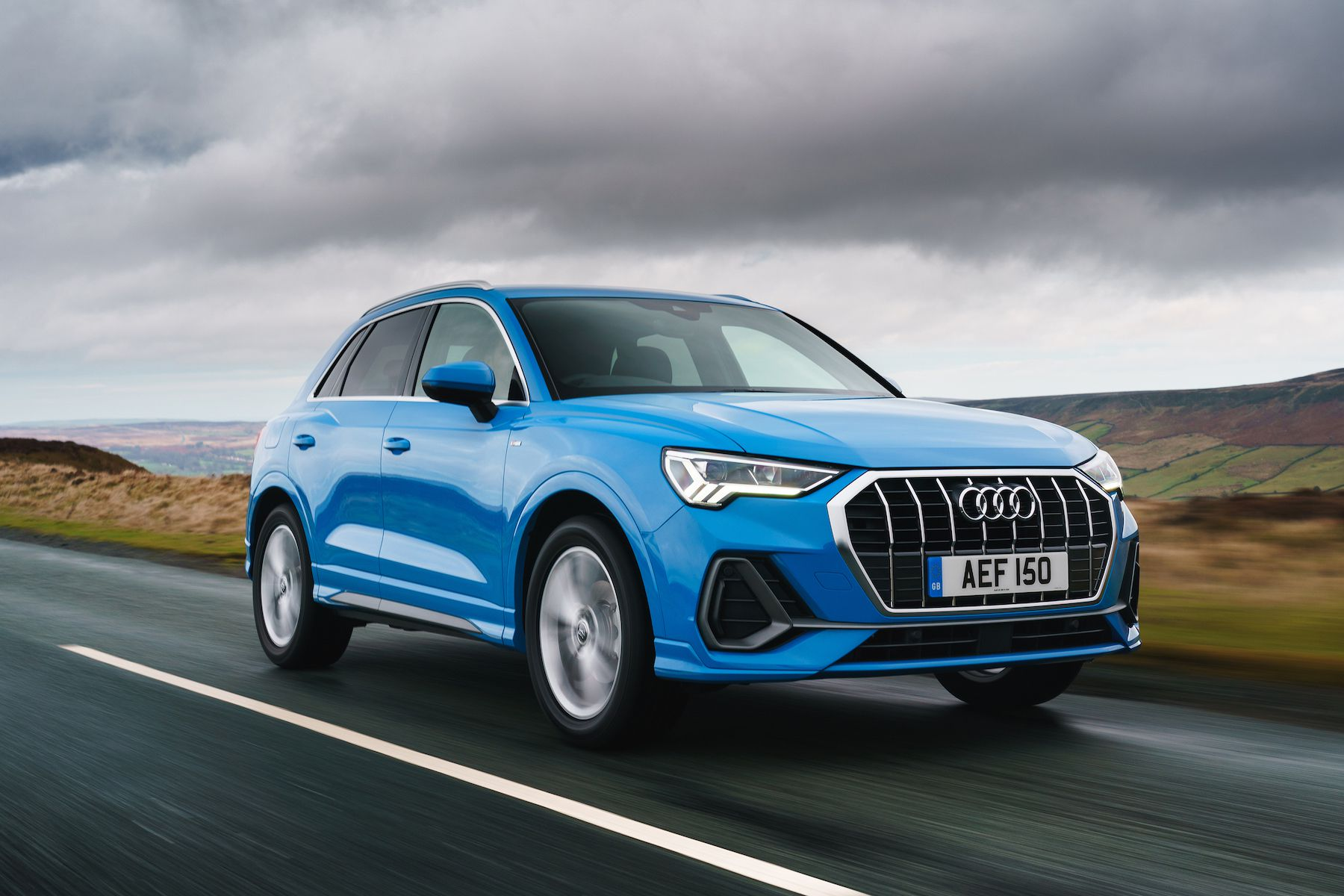 Blue Audi Q3 SUV on road from side front