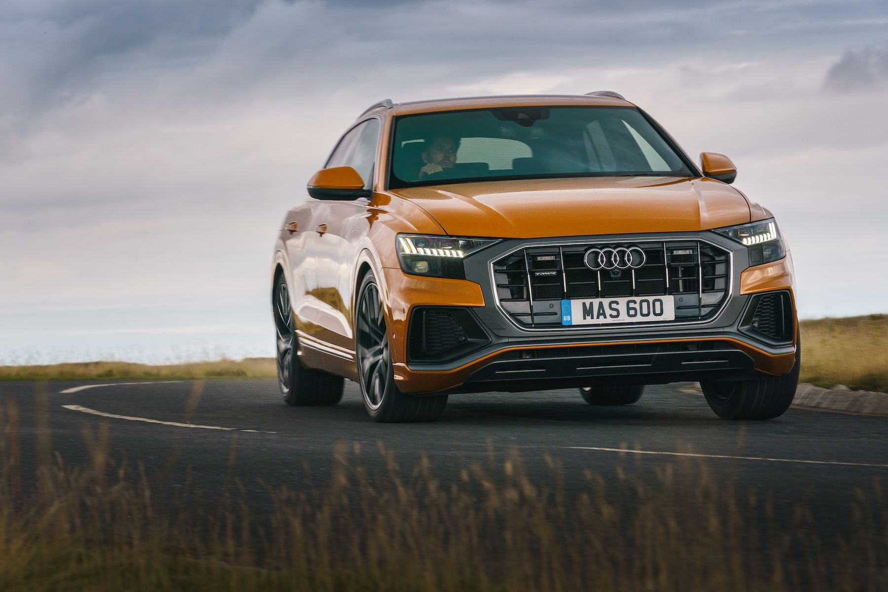 Orange Audi Q8 on road from side and front