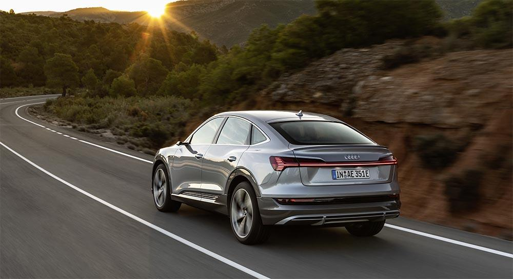 Rear view of Audi E-Tron Sportback driving on a road