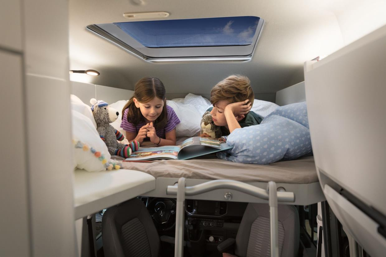 Two children tucked up in VW Grand Claifornia bunk bed