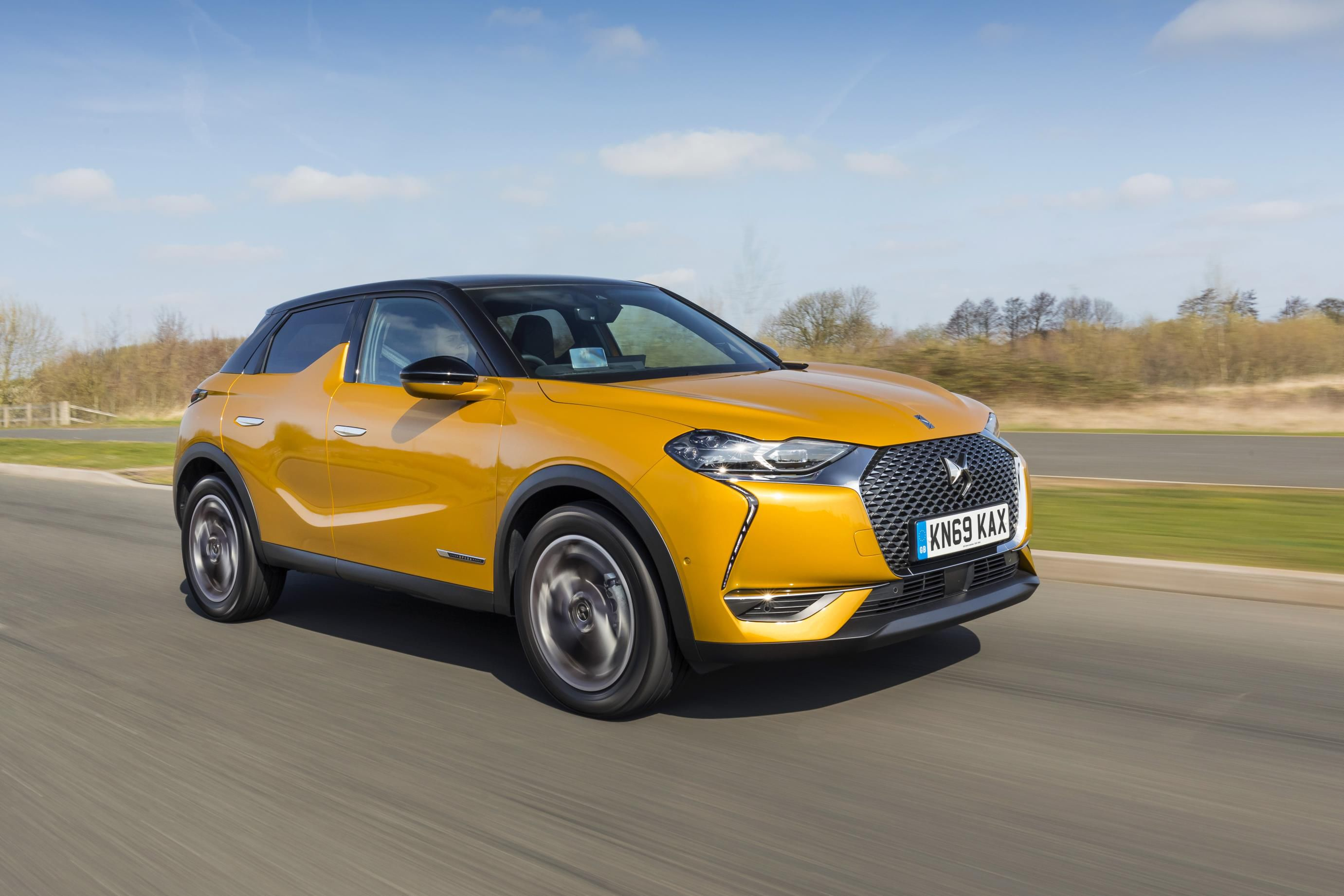 Metallic tangerine ornage DS3 CROSSBACK driving at speed down a road towards you