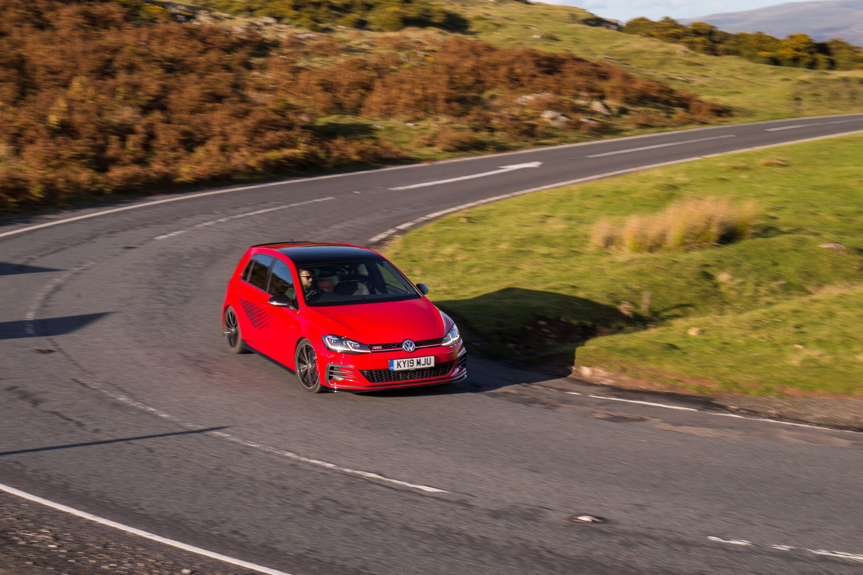 red golf driving on a windy road