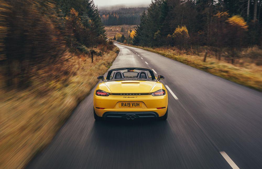 Yellow Porsche 718 Boxster driving through trees