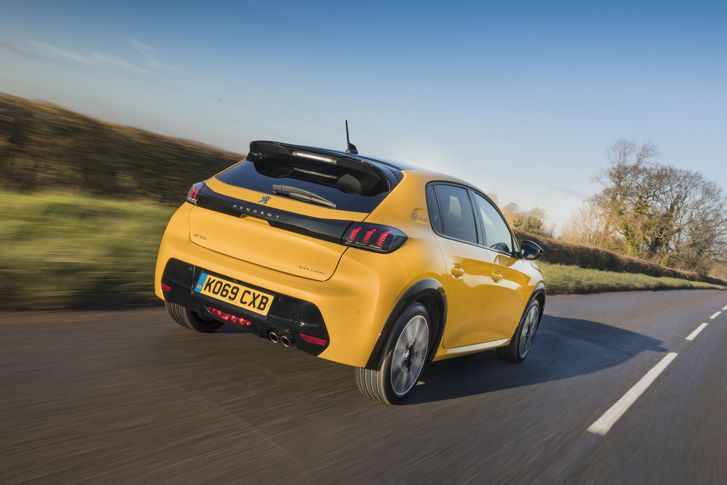 Rear view of a yellow Peugeot 208 driving on a road