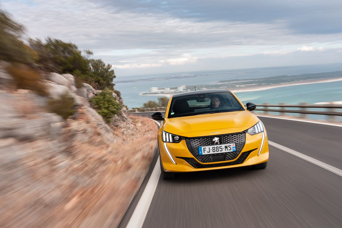 Front view of yellow Peugeot 208 with the beach behind it