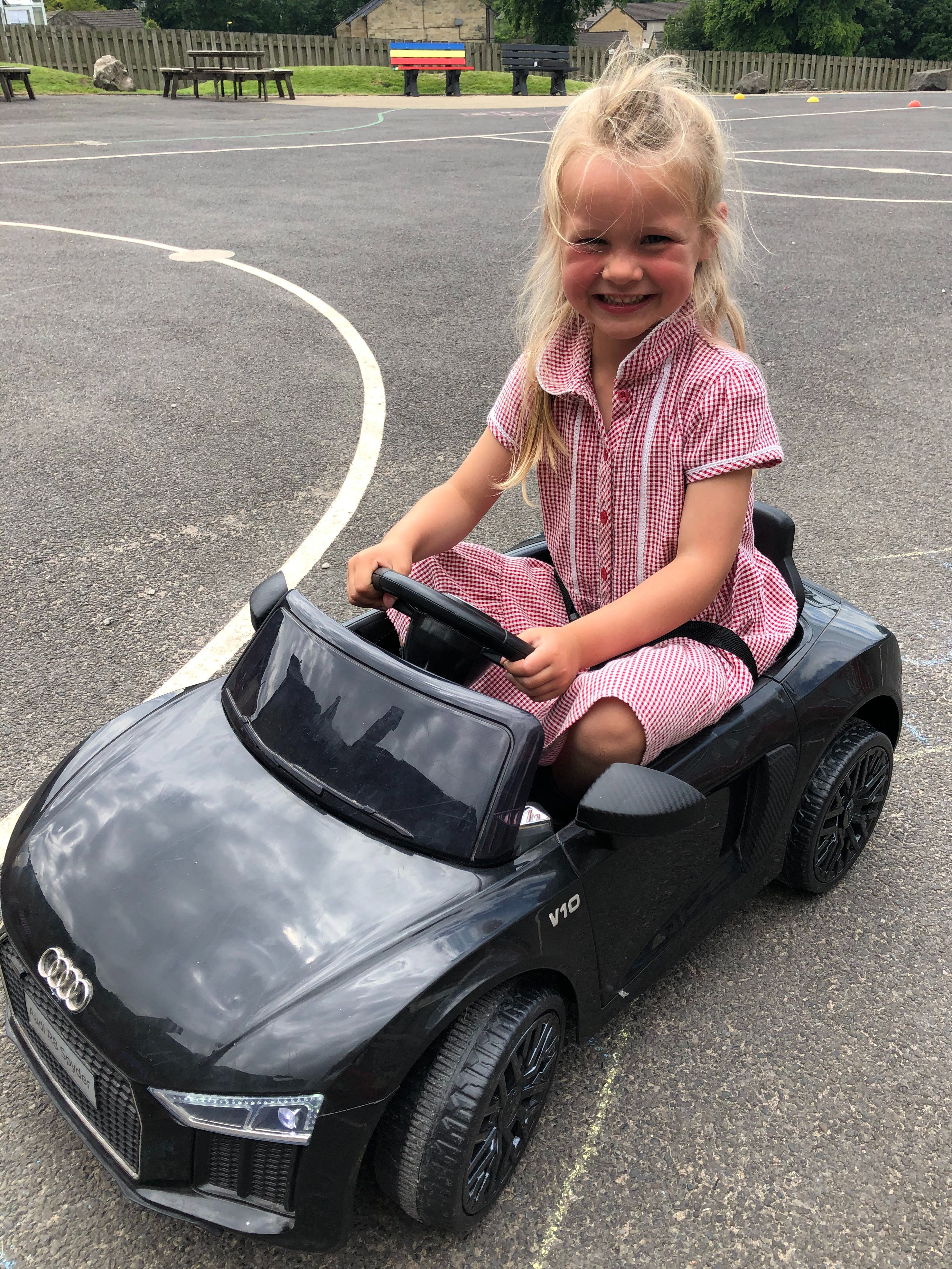 Girl on an Audi R8 toy