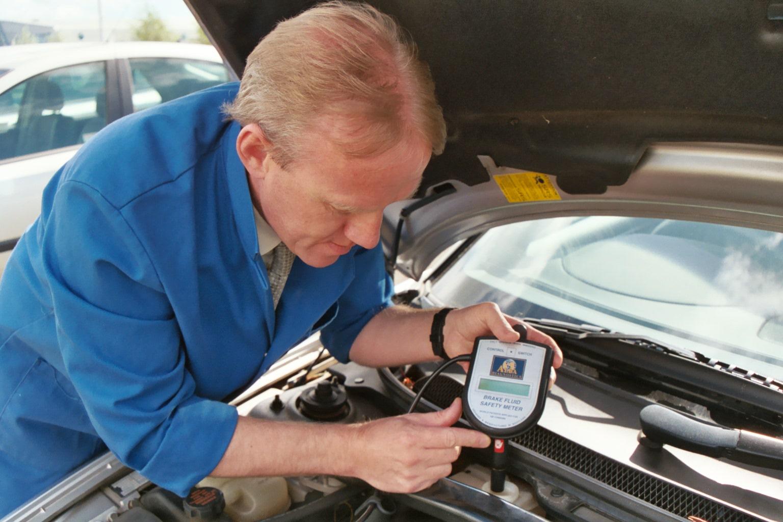Man checking brake fluid