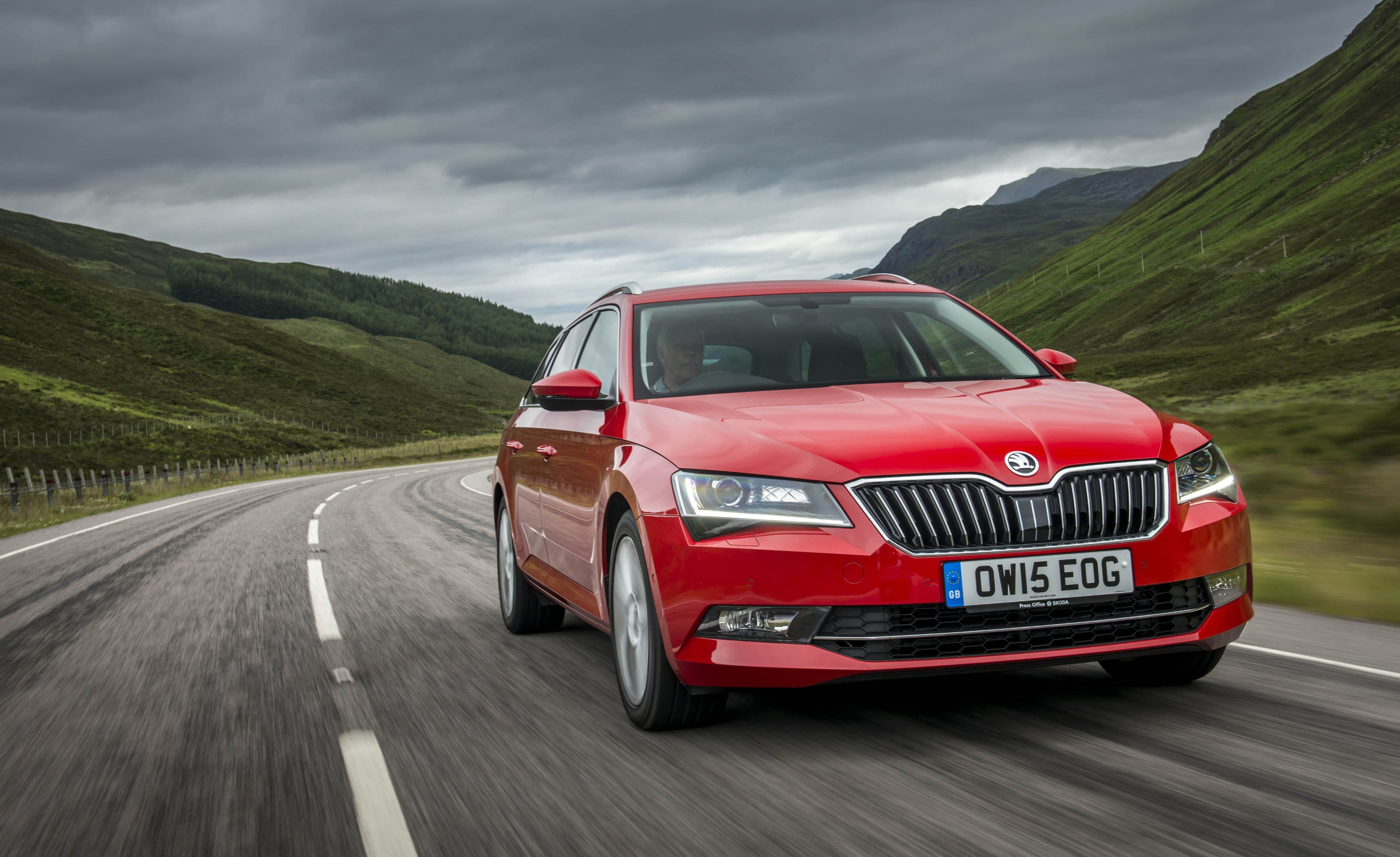 Red Skoda Superb driving on a road