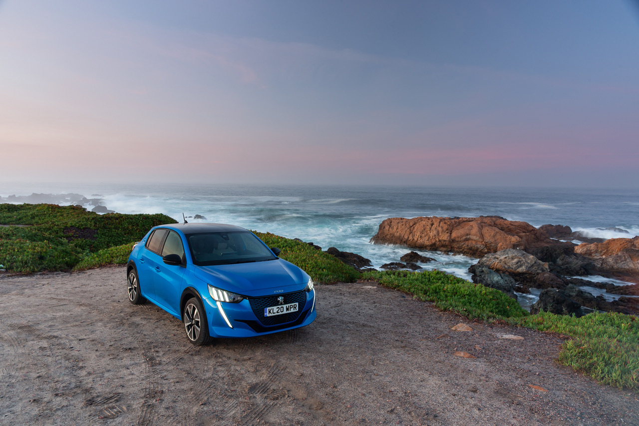 blue peugeot e208 parked by the coast