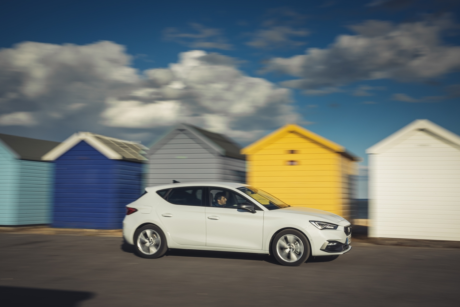 white seat leon driving in front of beach huts