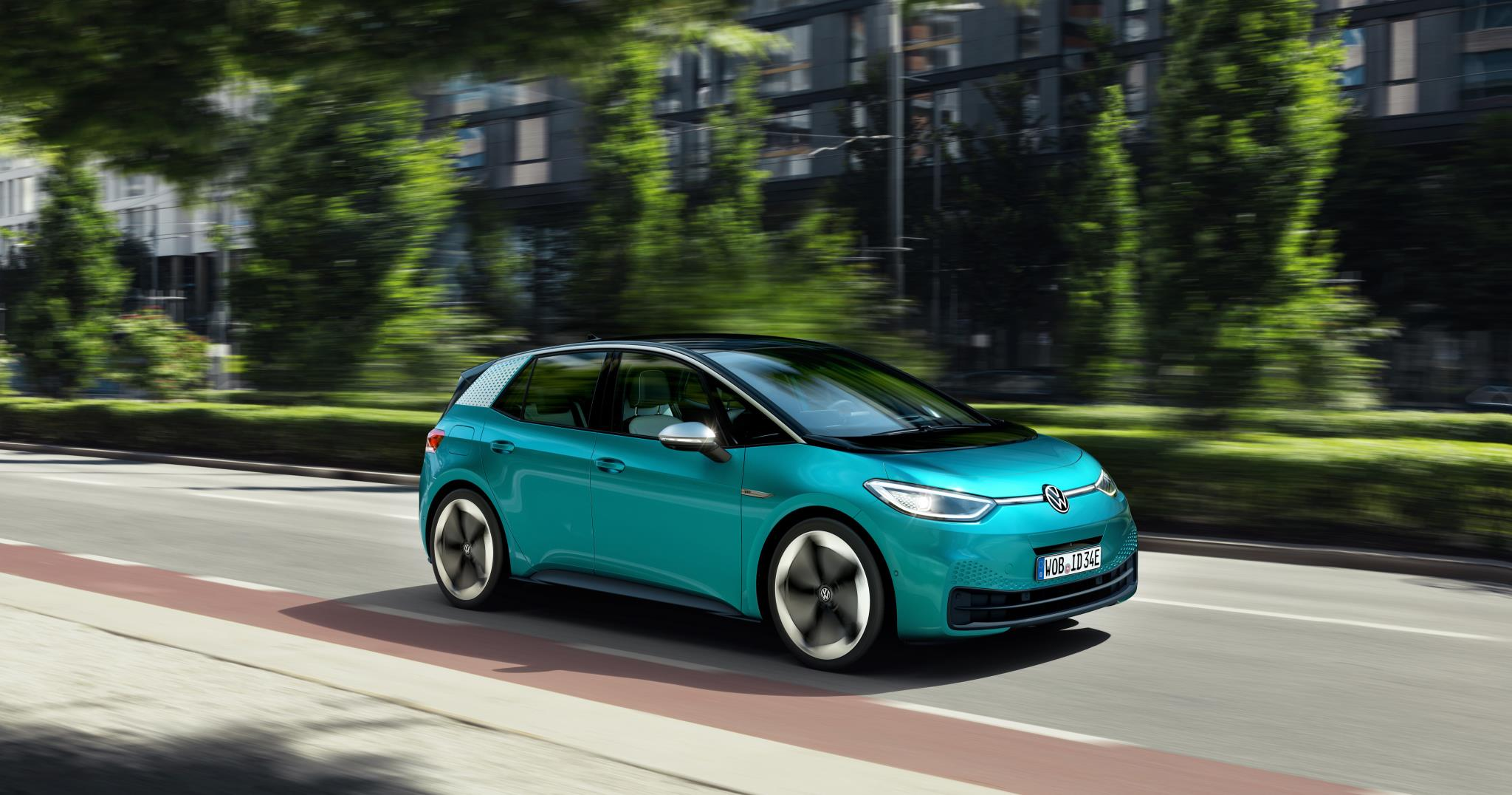 Bright turquoise blue Volkswagen ID 3 driving at speed
