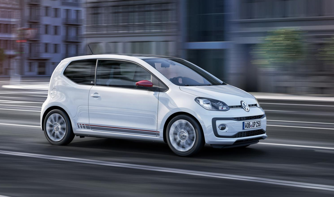 White Volkswagen up! moving at speed in city landscape