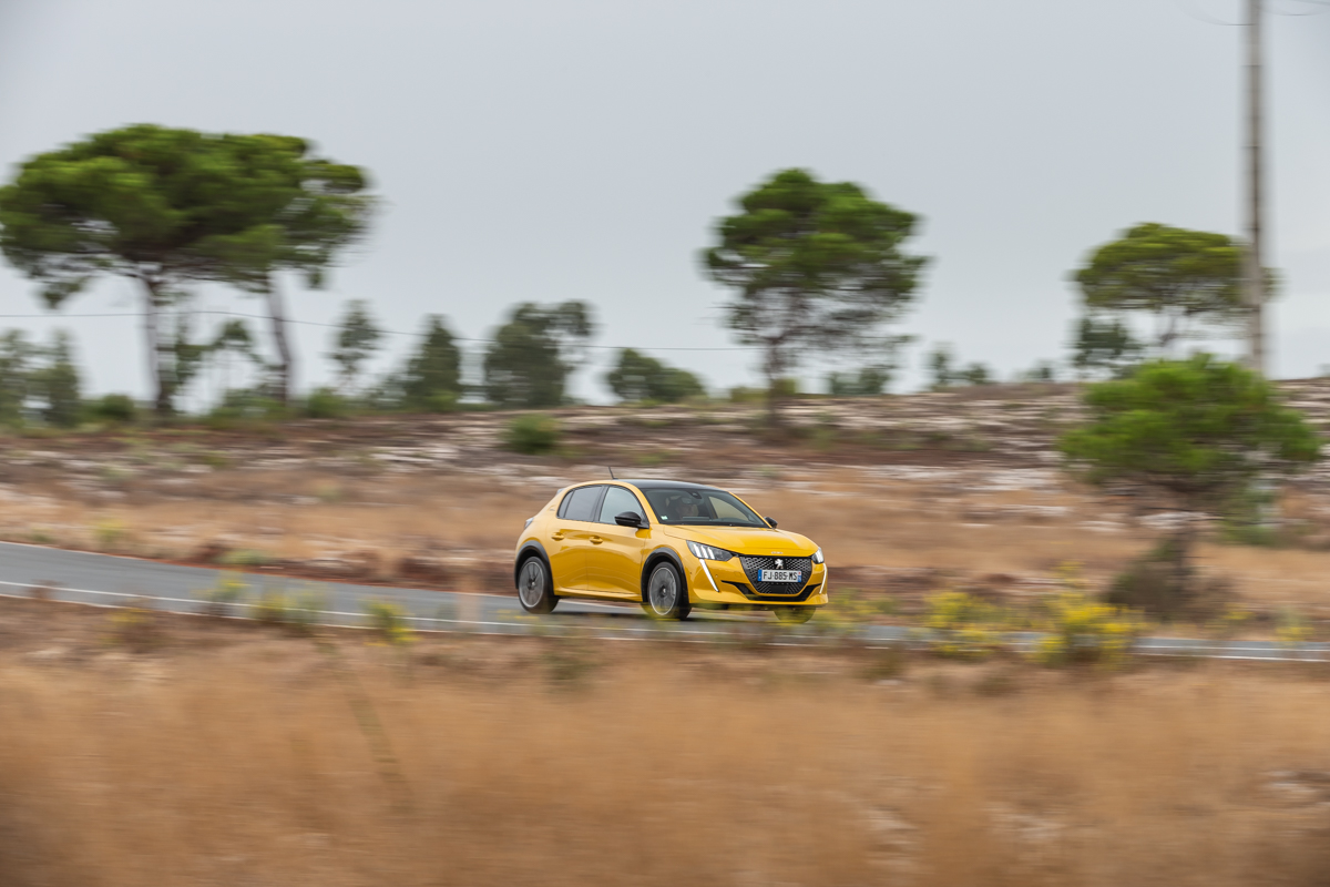 Yellow Peugeot 208 driving on a road