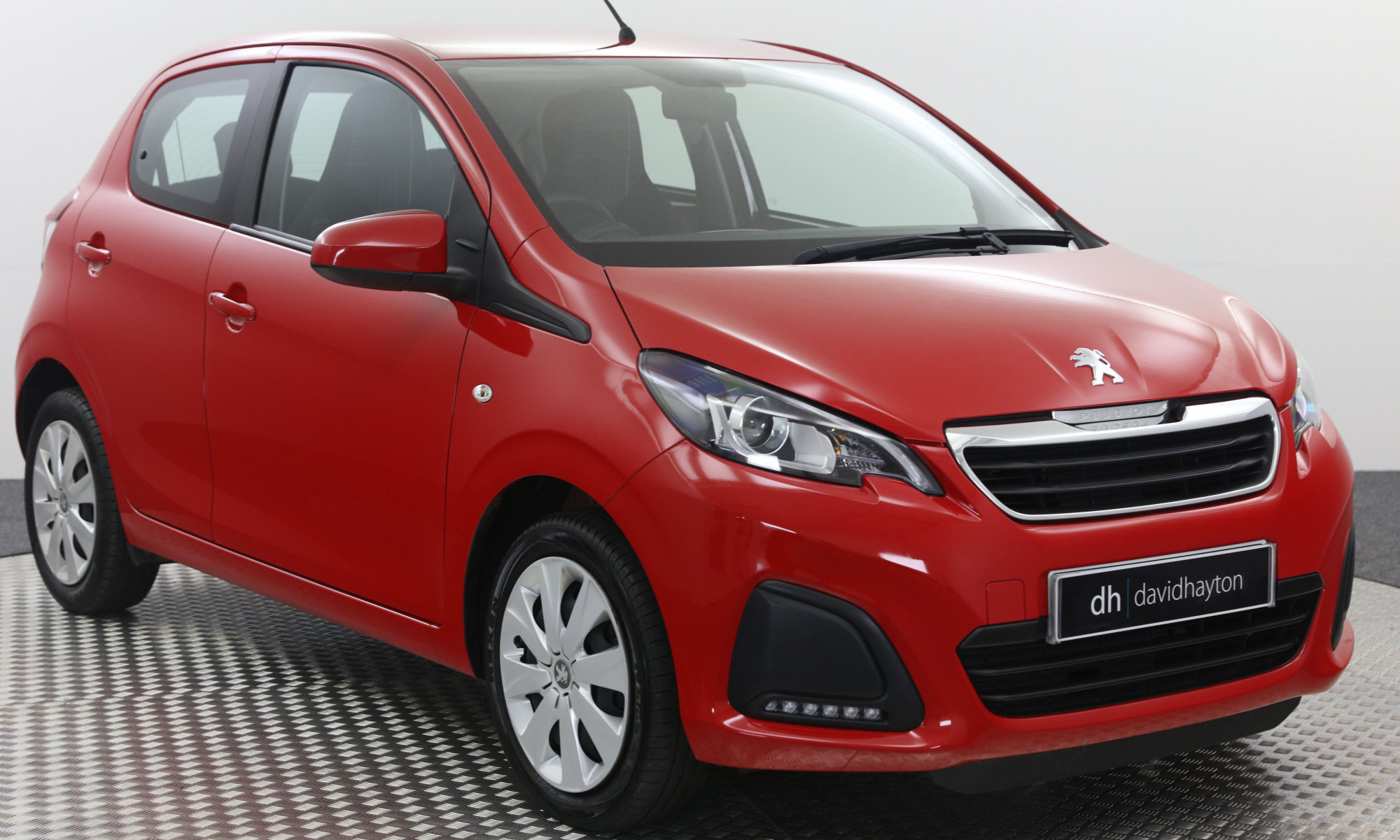 Red Peugeot 108 facing 3/4 right