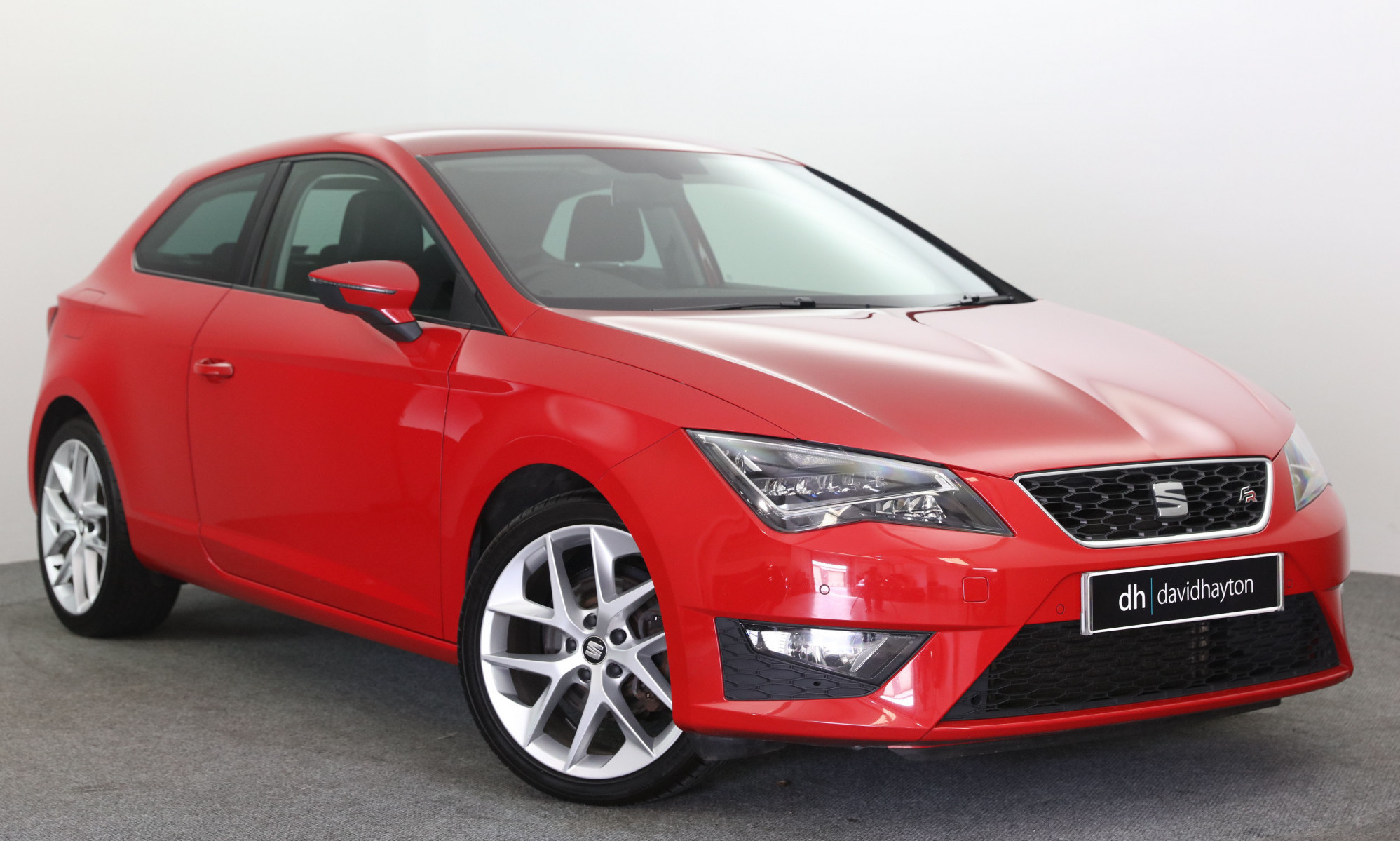 Red SEAT Leon facing 3/4 right