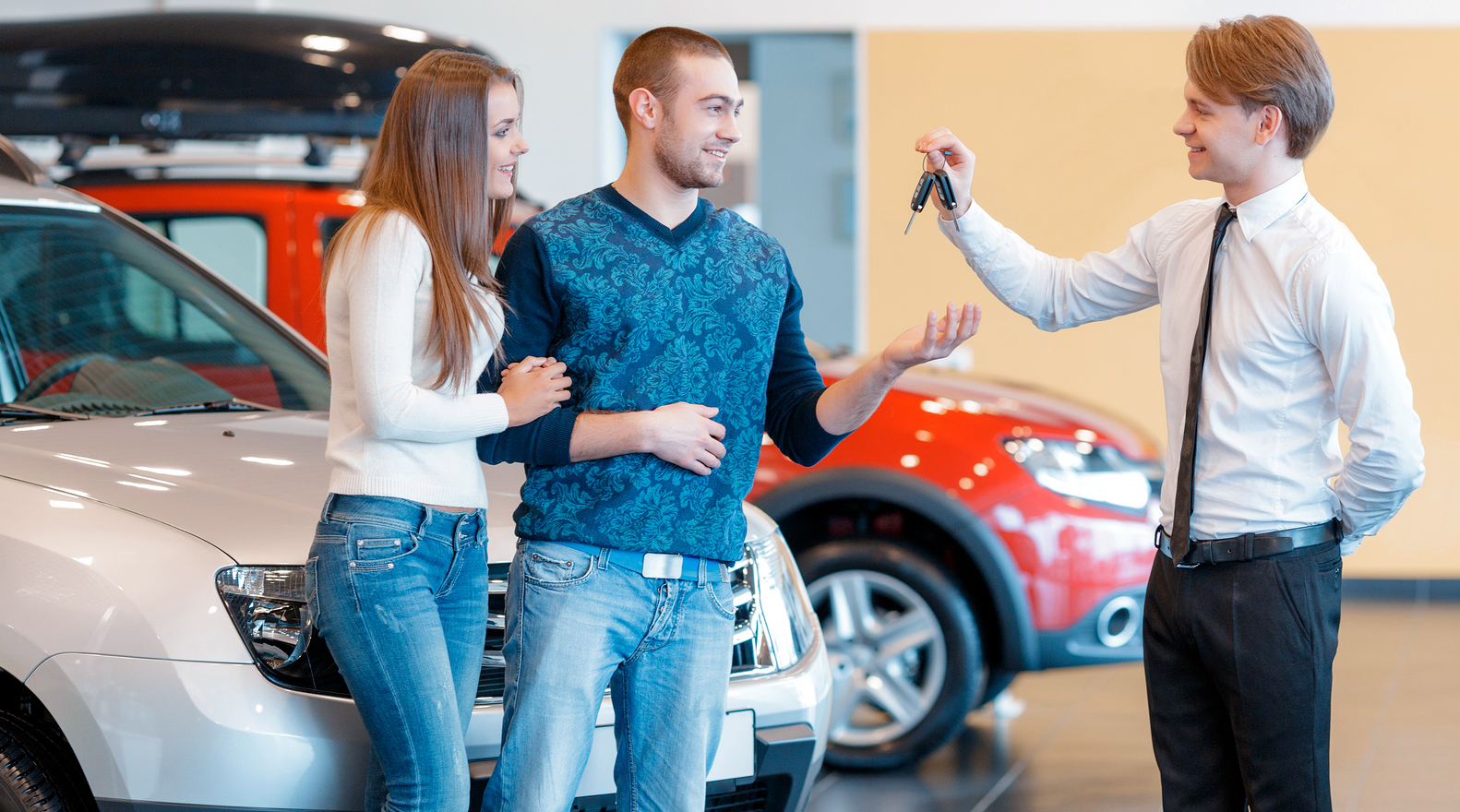 Smiling couple receiving car key from car sales man
